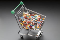 Shop cart with different colorful pills on black Stock Photo