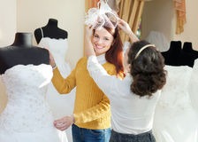 Shop consultant helps girl chooses white bridal outfit. At shop of wedding fashion. Focus on bride Stock Photo
