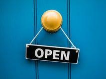 Shop door open sign. Local blue shop door with open sign over a brass door knob, London stock photos
