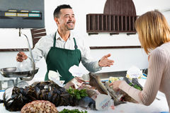 Shop employee cheerful selling fresh fish and chilled seafood Stock Photo