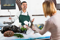 Shop employee cheerful selling fresh fish and chilled seafood. Shop employee smiling cheerful  selling fresh fish and chilled seafood to client Royalty Free Stock Photos