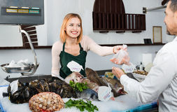 Shop employee happy beautiful selling fresh fish and chilled sea Royalty Free Stock Images
