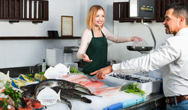 Shop employee happy beautiful selling fresh fish and chilled sea Stock Photography