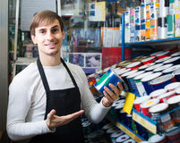 Shop employee posing near stand with wall paint Royalty Free Stock Image