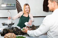 Shop employee smiling  selling fresh fish and chilled seafood Royalty Free Stock Photos