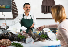Shop employee smiling selling fresh fish and chilled seafood Stock Photos