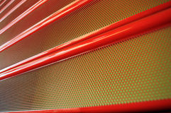 Shop facade enclosure system. Detail of red rolling shutter metallic steel door grating, closed, as industrial background stock image