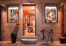 Shop-Front nachts mit Lichtern und altem Fahrrad in Rovinj Kroatien Lizenzfreies Stockbild