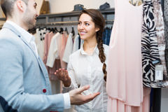 Shop girl helping client at boutique. Shop girl helping client to choose new garment at boutique Stock Photography