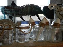 Shop glassware home related. Shop gift with glassware handmade wooden fish in a jar and ceramic fish maritiem Stock Photo