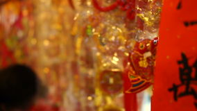 Shop hanging chinese new year decorations. Colorful red, gold and good words decorative pendants and paper around. Shop hanging chinese new year decorations