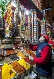 A shop keeper hangs a bunch of garlic bulbs in the Spice Bazaar in Istanbul in Turkey. royalty free stock photos