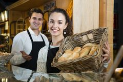 Shop-keeper man and woman with basket of loaf. Nice and friendly italian shop-keeper men and women with basket of loaf working behinde bakery disply in cafe royalty free stock images