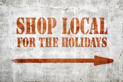 Shop local for the holidays graffiti. Shop local for the holidays - red graffiti sign with arrow on a white stucco wall stock images