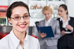 Shop manager. Portrait of smiling brunette businesswoman in eyeglasses staring at camera and two women on the background reading documents Stock Images