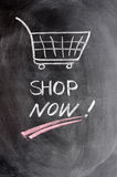 Shop now. Written in chalk with a drawing of shopping cart on blackboard Royalty Free Stock Images