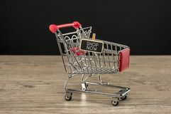 Shop now concept. Little trolley with wooden peg tag writing shop now Stock Image
