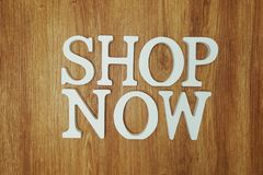 Shop Now word alphabet letters on wooden background. Top view of Shop Now word alphabet letters on wooden background stock images