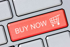 Shop online buy now business concept. Red shopping cart button on the computer keyboard stock image