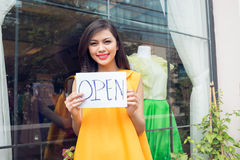 Shop is open. Close-up of a lovely shopkeeper opening up the shop on the foreground Royalty Free Stock Image