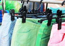 Shop pants hanging on a rack market. Royalty Free Stock Image
