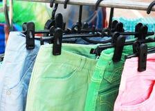 Shop pants hanging on a rack market. Royalty Free Stock Image