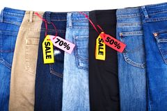 Shop sale of clothes, jeans of different colors blue, green, black on white background isolated close up royalty free stock images