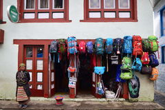 Shop selling colourful backpacks and other hiking related gears equipment along Everest Base Camp. The owner, in traditional sherpa clothing, standing next to Royalty Free Stock Photo