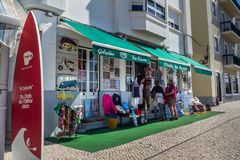 An shop selling on the main street in Nazare, Portugal. Poortugal shop selling nic-nacs in the street with surf board in the foreground Stock Photography