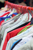 Shop shirts colorful fabric hanging on a rack. Shop shirts colorful fabric hanging on a rack Royalty Free Stock Photography