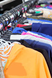 Shop shirts colorful fabric hanging on a rack. Royalty Free Stock Photo