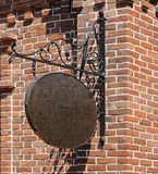 Shop sign. Blank, dark, shop sign hanging in a wrought iron bracket from a brick wall Stock Image