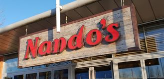 Shop sign for Nandos chicken restaurant royalty free stock image