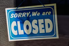 Shop sign with text: sorry, we are closed. Photography of a Shop sign with English text: sorry, we are closed behind a glass shop door Royalty Free Stock Photo