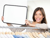 Shop sign woman. Small retail business owner showing blank sign in clothing store. For shopping or sale copy. Beautiful young mixed race Caucasian / Chinese Stock Photo