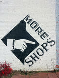 Shop Signage. A black mural on a white brick building directing folks to shops around the corner. Hand points to the right stock image