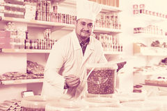 Shop staff standing near containers with olives in flavoured bri. Happy shop staff standing near containers with olives in flavoured brine Royalty Free Stock Photos