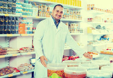 Shop staff standing near containers with olives in flavoured bri. Smiling  shop staff standing near containers with olives in flavoured brine Royalty Free Stock Photo