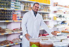 Shop staff standing near containers with olives in flavoured bri. Smiling  shop staff standing near containers with olives in flavoured brine Stock Image