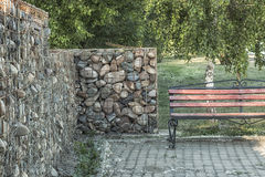 Shop and stone wall in the park. Stone wall with an iron grate and a bench near the trees in the park Royalty Free Stock Photo