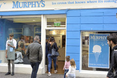 Shop Street, Galway, Ireland June 2017, Murphy`s ice cream shop,. Guy offering free taste and a family entering the shop Stock Photos
