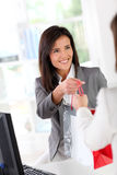 Shop tender giving shopping bag to customer Royalty Free Stock Images