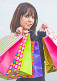 Shop til she drops. Sale bargains. An image of a girl with bags full of purchases: all bargains  bought in the sales Stock Photo