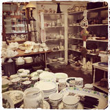 Shop with vintage dishware. Interior of a shop with vintage dishware. Sepia toned Royalty Free Stock Image
