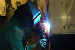 Shop Welder. A welder wearing a welding mask working in a shop fabricating industrial stainless steel Stock Photos