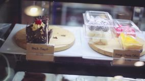 Shop window in a bakery or grocery shop with wide choice or range of various deserts with beautiful blurred bokeh on. Shop window in a bakery or grocery shop stock video
