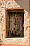 Shop window. View through the shop window of a traditional greek house  on hanging women's garments. Fiskardo, Kefalonia, Greece Royalty Free Stock Photo