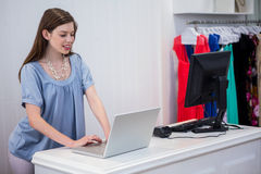 Shop worker using laptop by the till Stock Images