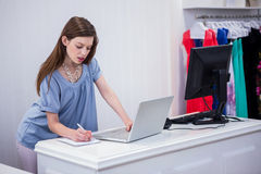Shop worker using laptop by the till Royalty Free Stock Photos