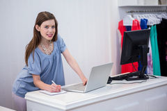 Shop worker using laptop by the till Royalty Free Stock Photography